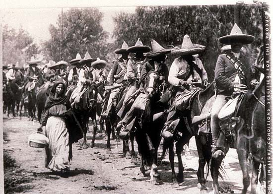 Mexico, Revolution, Photo of a woman walking next to a line of mounted Zapatista. Photo by Agustín Victor Casasola (1874-1938). Cf. http://content.cdlib.org/ark:/13030/hb1p300718/?layout=metadata&brand=calisphere