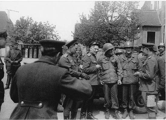 A photo of the same scene, taken by American Private Igor Belousovitch who was in Major Craig's patrol (Craig is the leftmost American – they all put helmets on), shows most probably Ustinov working. Source: The Moscow Times