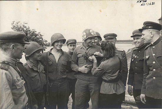 Nurse Lyubov Kozinchenko gives flowers to paramedic Carl Robinson. Leftmost is the commander of the 6th Rifle Company Lieutenant Goloborodko, rightmost is the chief of the division artillery headquarters Major Anatoliy Ivanov and next to him is the commander of the 175th Guards Rifle Regiment Lieutenant Colonel Aleksandr Gordeyev.